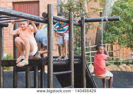 School kids playing on monkey rack at playground