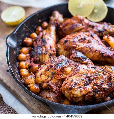 Harissa roasted chicken in black pan with lemon and corn
