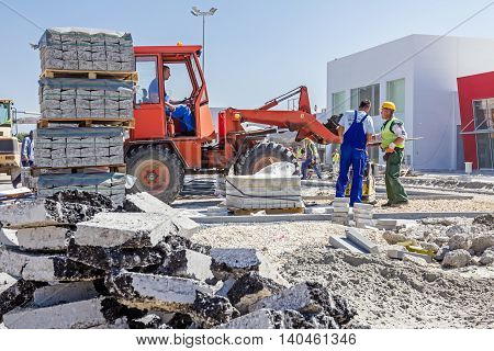 Zrenjanin Vojvodina Serbia - September 14 2015: Workers are helping forklift to place on right place plate compactor machine.