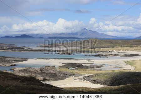 This is a view over Sanna Bay in West Ardnamurchan, Scotland. The beach is visible in the mid-distance, and The Small Isles of Muck, Rum and Egg are seen in the background. The sky is blue, with white clouds. The picture was taken in the month of May.