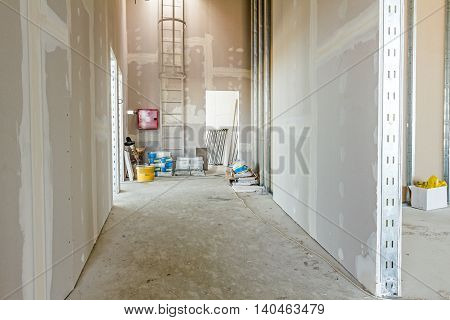 View through corridor of gypsum plasterboard walls under construction.