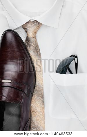Men's classic accessories: shirt tie shoes as a backdrop top view