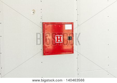 Red fire hydrant cabinet with extinguish equipment is placed in a dry wall.
