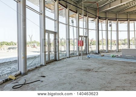 View on indoor construction site of unfinished modern large showroom. poster