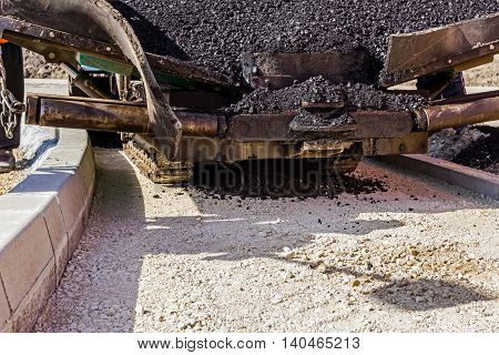 Front view on asphalt laying machine full of fresh asphalt at road construction site. Hot asphalt is spreading from paver machine on prepared ground.