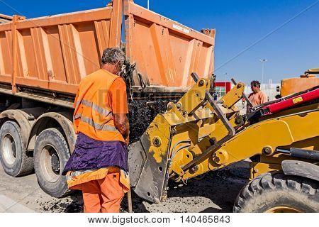 Zrenjanin Vojvodina Serbia - September 14 2015: Dumper truck is unloading asphalt in excavator range at construction site.