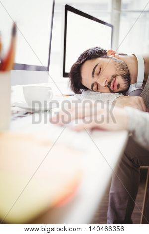 Young tired businessman taking nap in creative office