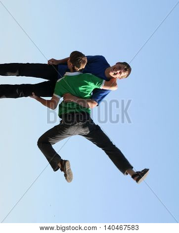 Man holding another man in strange pose. Gravitation not working for them