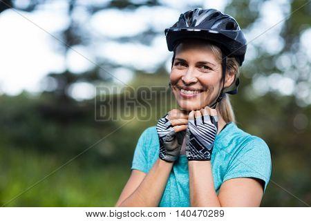 Portrait of smiling female athletic wearing bicycle helmet