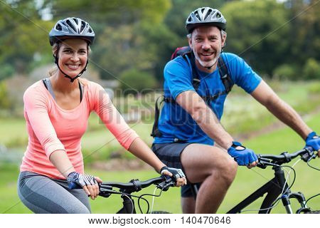 Smiling athletic couple cycling on the road