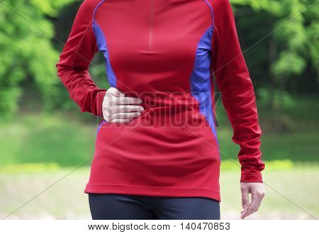 Side stitch - woman runner side cramps after running. Jogging woman with stomach side pain after jogging work out.
