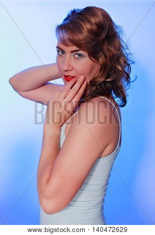 Sensuous young female holding her hands next to her face smiling charmingly at you