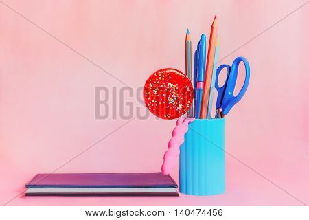 Blue pencil-box with pencils scissors and red round candy beside notepad on a pink background. Selective focus.