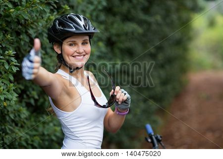 Portrait of smiling woman showing thumbs up