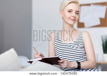 Calm time. Thoughtful relaxed adorable woman looking at the camera while sitting on the sofa and writing in the notebook