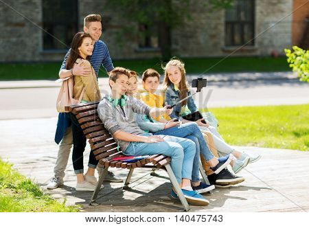 education, high school, technology and people concept - group of happy teenage students or friends taking selfie by smartphone and monopod