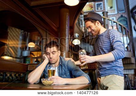 people, leisure, friendship and party concept - man with beer cheering up his sad drunk friend at bar or pub