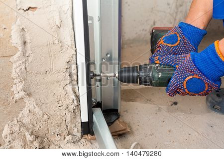 Garage doors installation. Worker use automatic screwdriver to fix a bolt