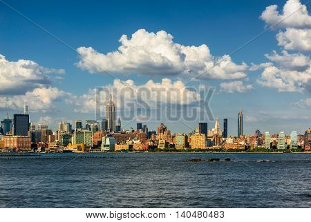 Manhattan Midtown West skyscrapers and Hudson River with passing clouds. Cityscape of a summer afternoon in New York City with view of Midtown and West Village