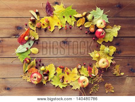 nature, season, advertisement and decor concept - set of autumn leaves, fruits and berries on wooden table