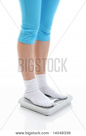 young athletic girl standing on the scales