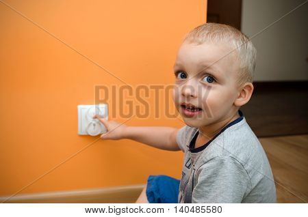 Child Near To The Socket. Electrical Security Of Ac Power For Babies