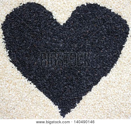Sesame seeds black and white heart close up