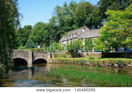 BIBURY, UNITED KINGDOM - JULY 20, 2016 - View along the River Coln towards the stone bridge with The Swan Hotel to the rear Bibury Cotswolds Gloucestershire England UK Western Europe, July 20, 2016.