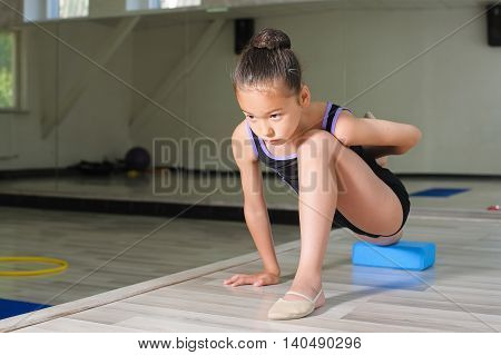 Stretching Little japanese Girl. Attractive beautiful Asian girl doing gymnastics exercises in hall rhythmic gymnastics. White wall in the background.