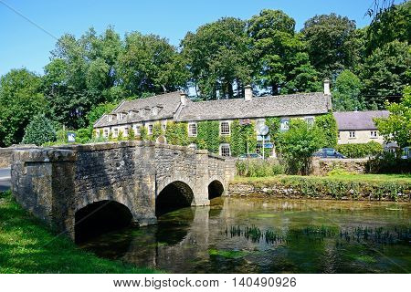 BIBURY, UNITED KINGDOM - JULY 20, 2016 - Pretty Cotswold stone bridge across the River Coln with The Swan Hotel to the rear Bibury Cotswolds Gloucestershire England UK Western Europe, July 20, 2016.