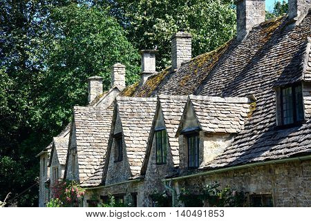 BIBURY, UNITED KINGDOM - JULY 20, 2016 - View of the dormer windows and roof of Arlington Row cottages Bibury Cotswolds Gloucestershire England UK Western Europe, July 20, 2016.