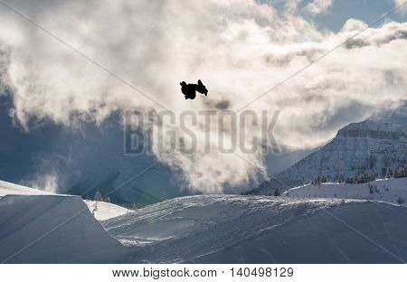 Snowboarder performing a flip off a large jump in the mountains