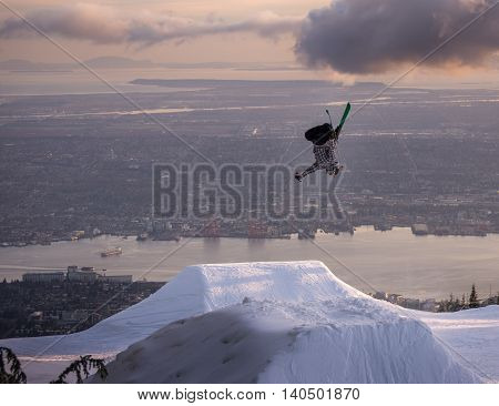 Freestyle skier performs backflip mute grab on jump over city