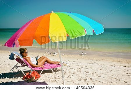 Beautiful Woman with Multi-Color Umbrella Enjoying a Day at the Beach on Anna Maria Island Florida