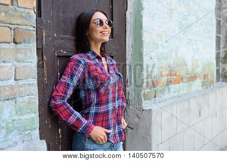 There is no place like home. Happy young woman is standing near old building and relaxing. She is leaning on door and smiling
