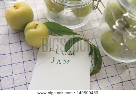 The words plum jam on white paper with fresh plums some in jars on a blue and white dish towel