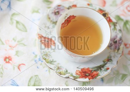 Cup of tea in floral cup on flower print cloth