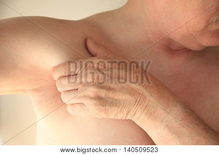 Older man has a hand next to his armpit area.