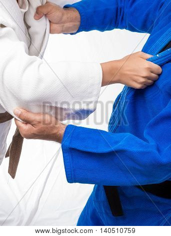 Judo Gripping between female judo brown belt and her sensei black belt isolated on white background poster