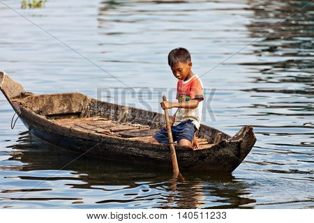 SIEM REAP, CAMBODIA-NOVEMBER 17, 2011: An unidentified boy on a boat floating on Tonle Sap lake in Siem Reap. Tonle Sap is the largest lake in SE Asia peaking at 16kkm2