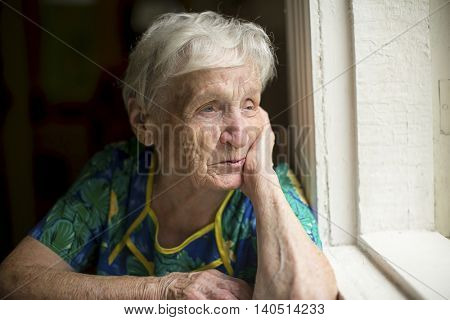 An elderly lady skeptically looking out the window.