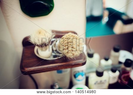 Brush shaving set in barber shop. Technique of selective focus.