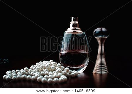 female perfume and jewelry in black background
