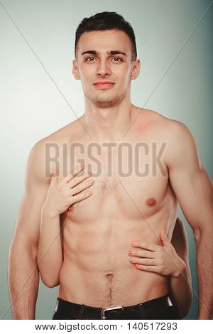 Sexy passionate couple lovers in studio. Woman hands embracing handsome half naked semi nude man. Love and passion.