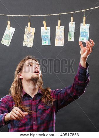 Currency exchange concept. Man worker check verify money cash. Payment hang on laundry line.