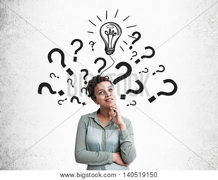 Black woman standing near wall with light bulb and multiple question marks pictured on it. Concept of finding solution for problem