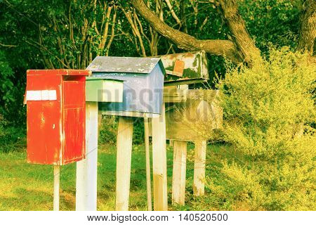 Retro style image old letterbox line up different colors and shapes red green blue surrounded by trees and bush