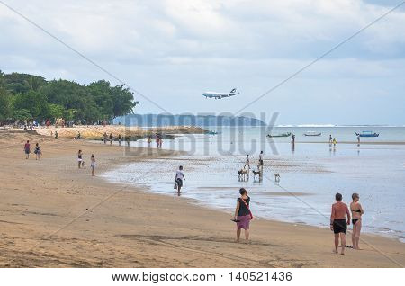 Bali,Indonesia-May 28,2010:Foreign tourists walk along at south Kuta beach,the German Beach.Locally known as the Pasih Perahu Beach,the German Beach is located near the Ngurah Rai Airport runway.