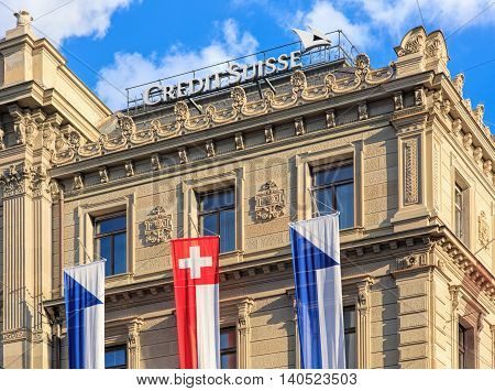 Zurich, Switzerland - 30 July, 2016: upper part of the Credit Suisse building on Paradeplatz square, decorated with flags of Switzerland and Zurich. Credit Suisse Group is a Swiss multinational financial services holding company headquartered in Zurich.