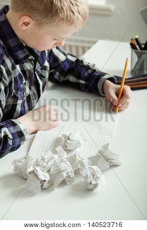 Young Teenage Boy Battling To Complete Homework